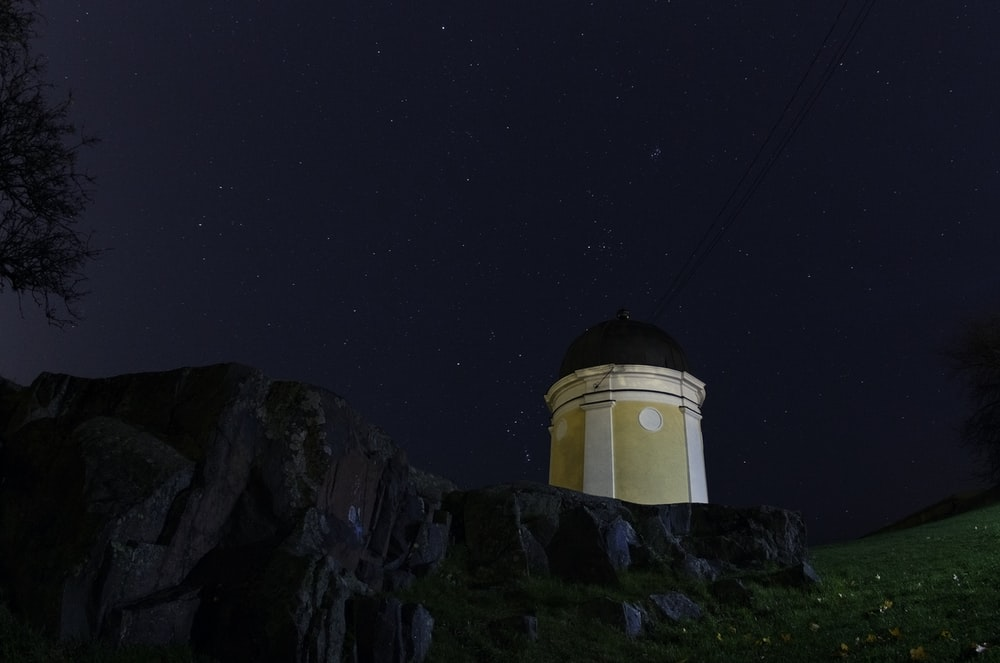 beige and black lighthouse on hill with starry sky