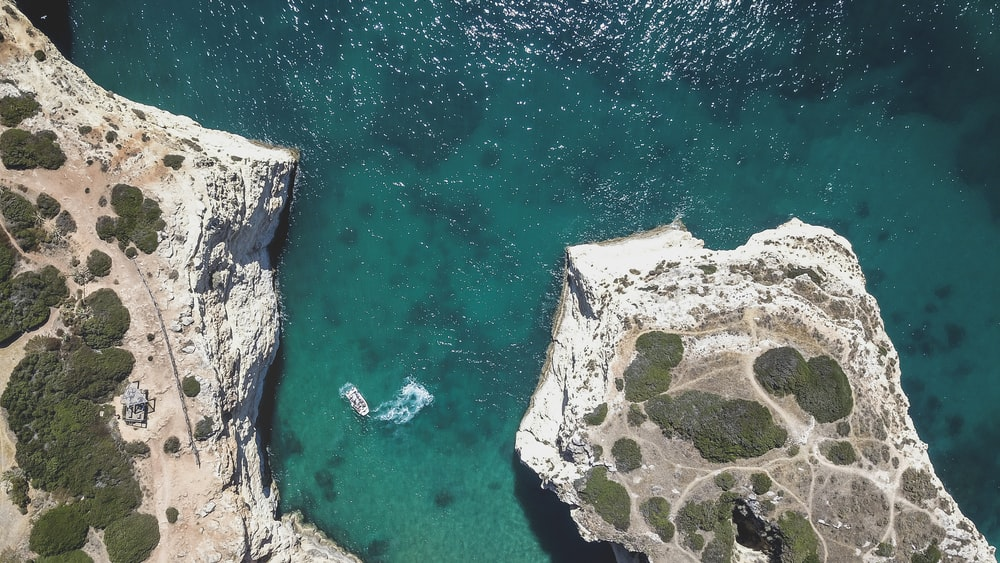 aerial photography of rock formation mountain near sea