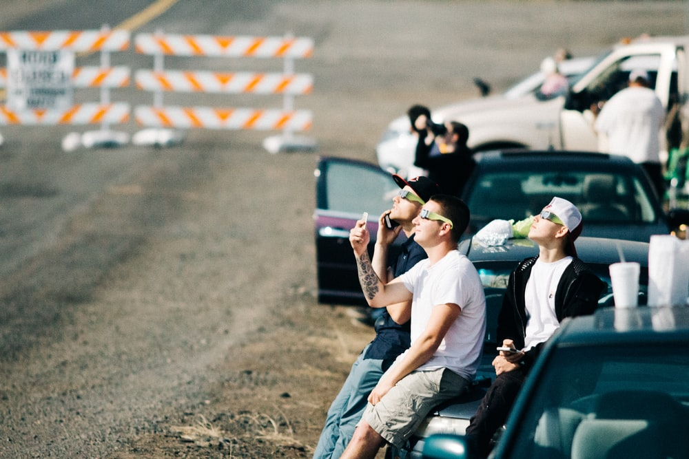 group of people sitting on car while watching air show