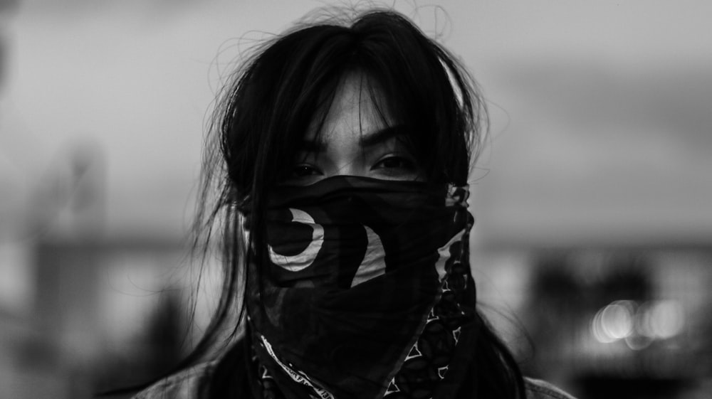 person wearing black mask in grayscale photography