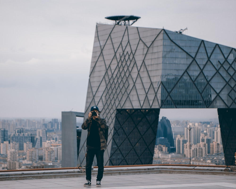 man taking picture while standing near gray building during daytime