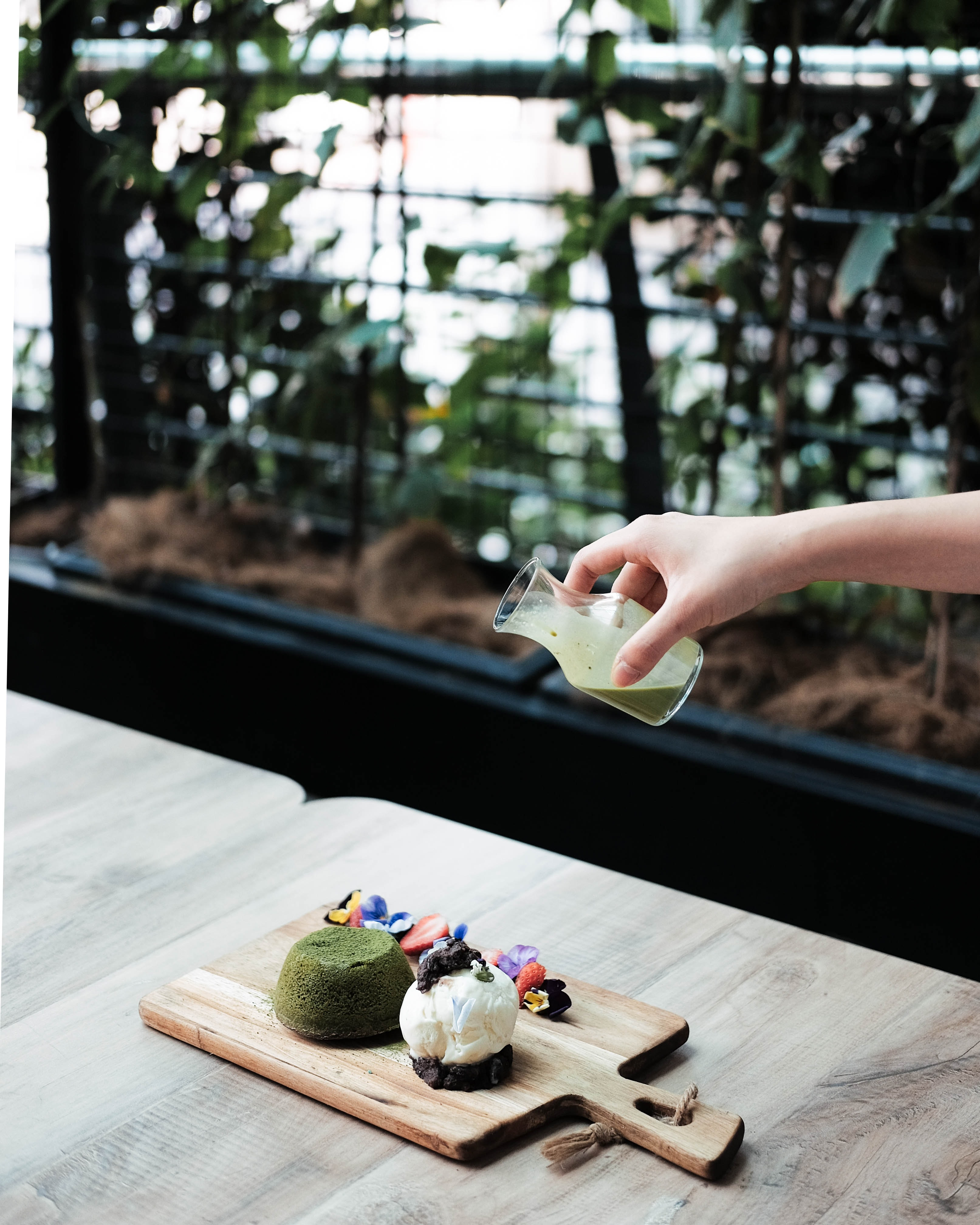person pouring green liquid on pastries