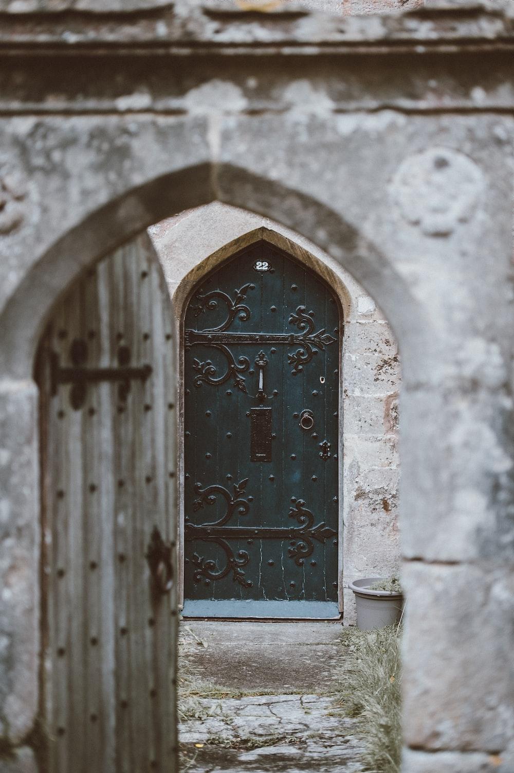 opened gray wooden door with closed green wooden door at the distance