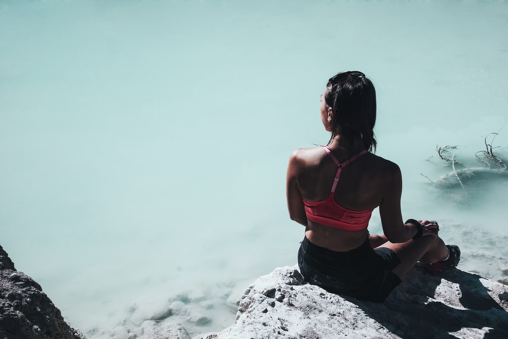 woman in pink sports bra sitting on rock near body of water at daytime