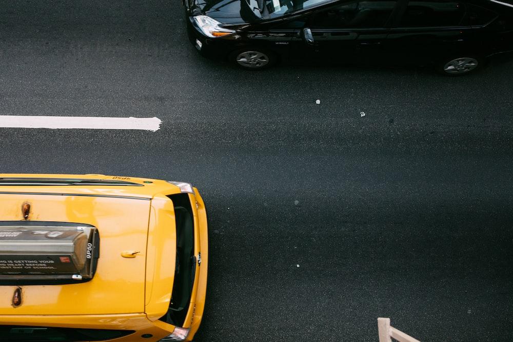 yellow car beside a black car on a black road