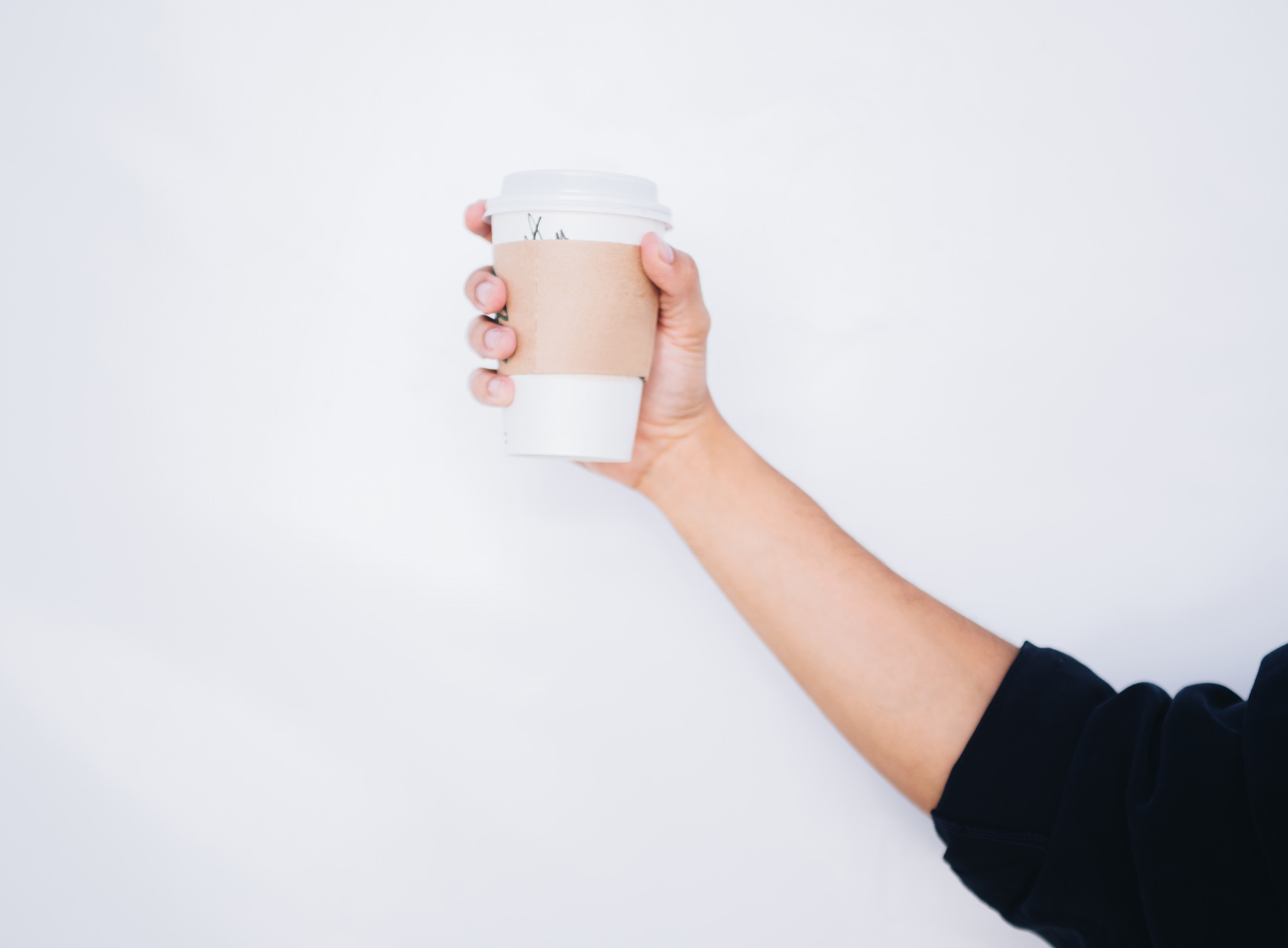 A coffee cup is held dramatically