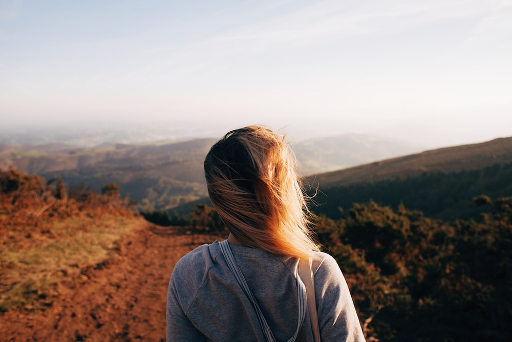 woman standing while looking on mountain range