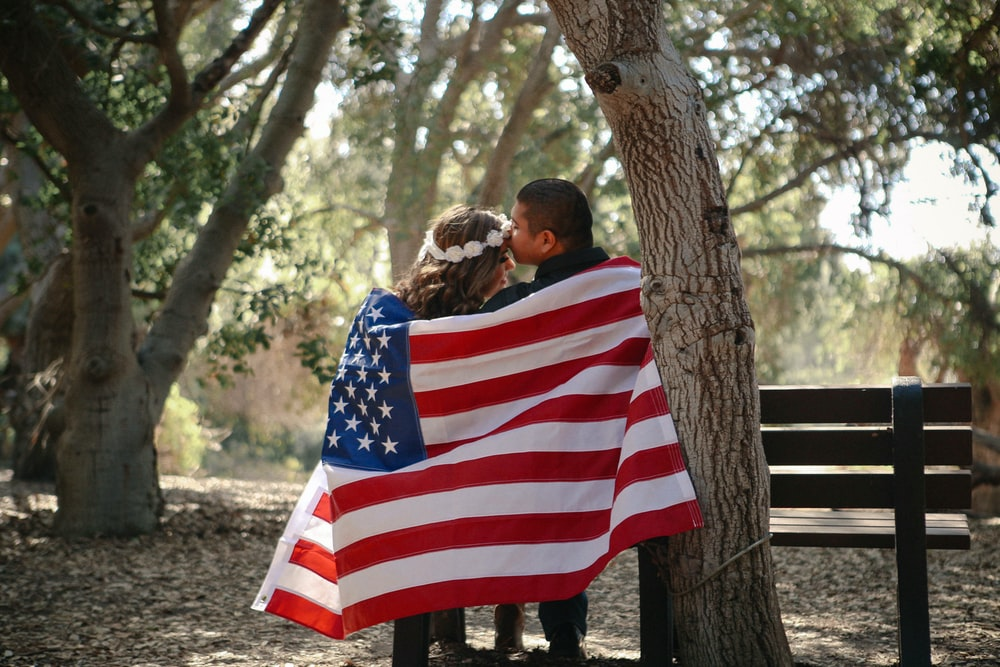 man kissing woman's forehead with American flag wrap around them during daytime