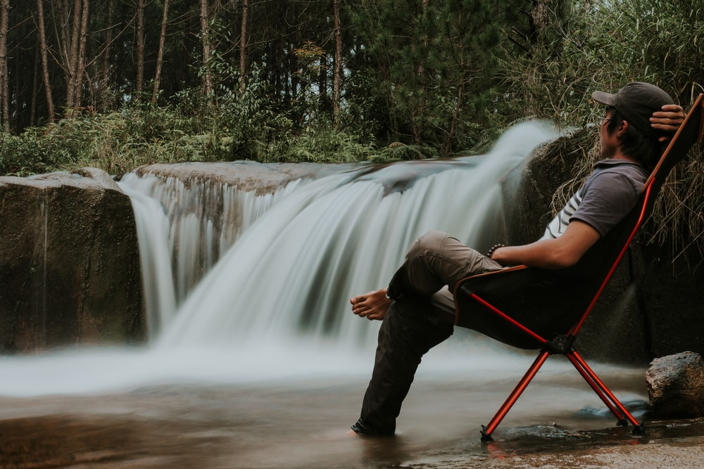 man sitting on folding chair watching the waterfalls during day