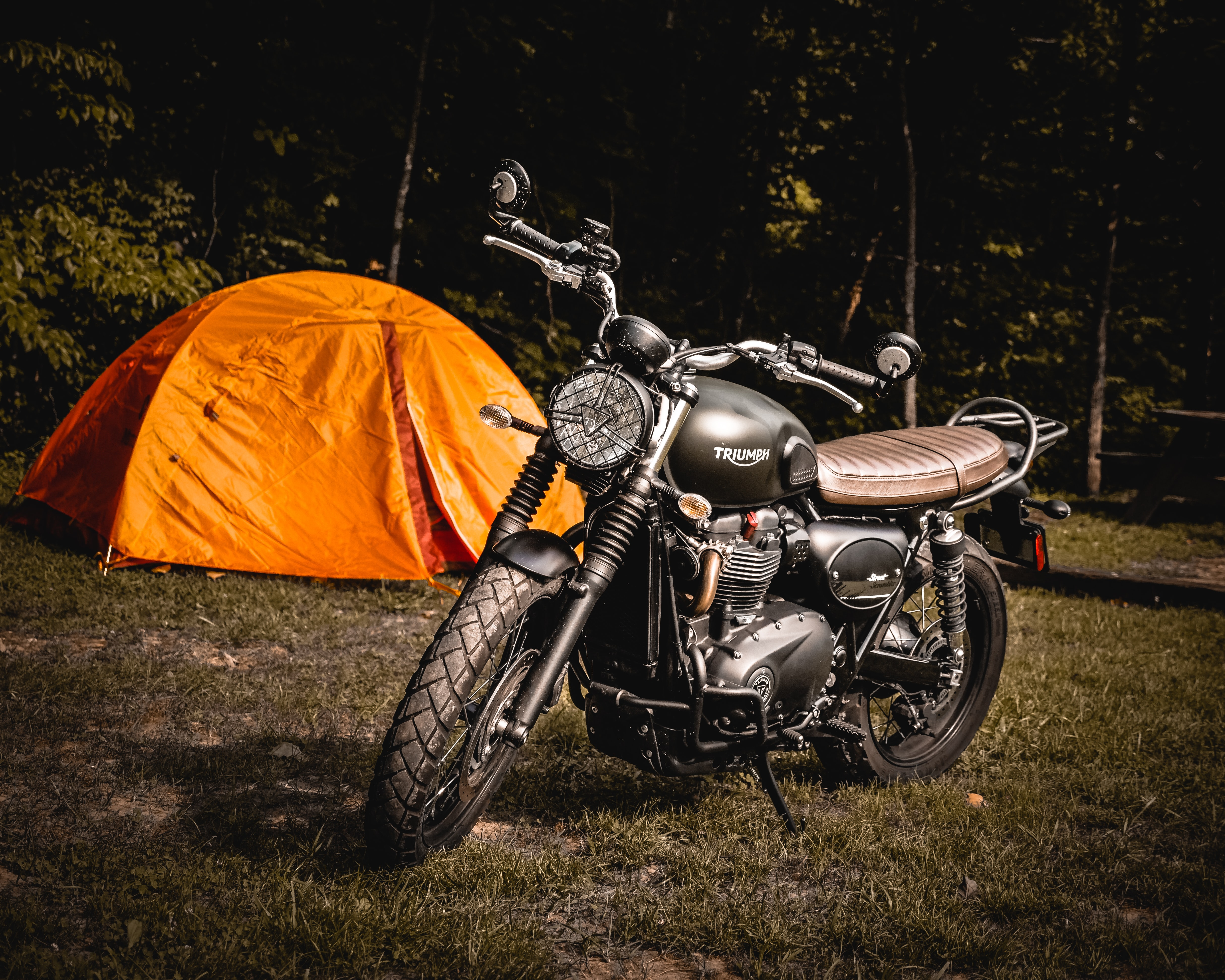 brown naked motorcycle parked beside orange camping tent