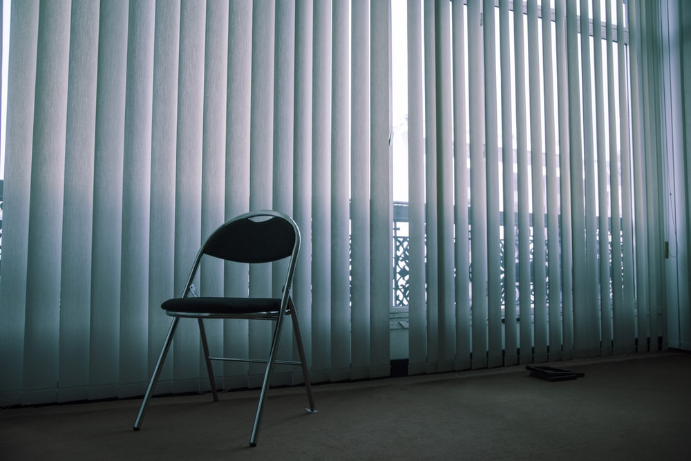 gray folding chair near white window blinds