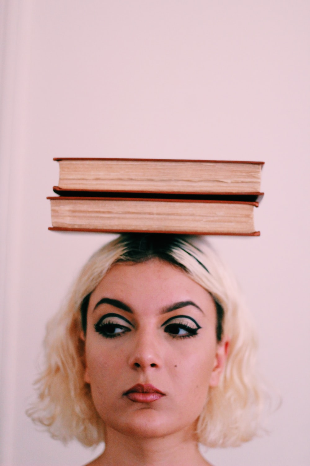 two books on top of woman's head