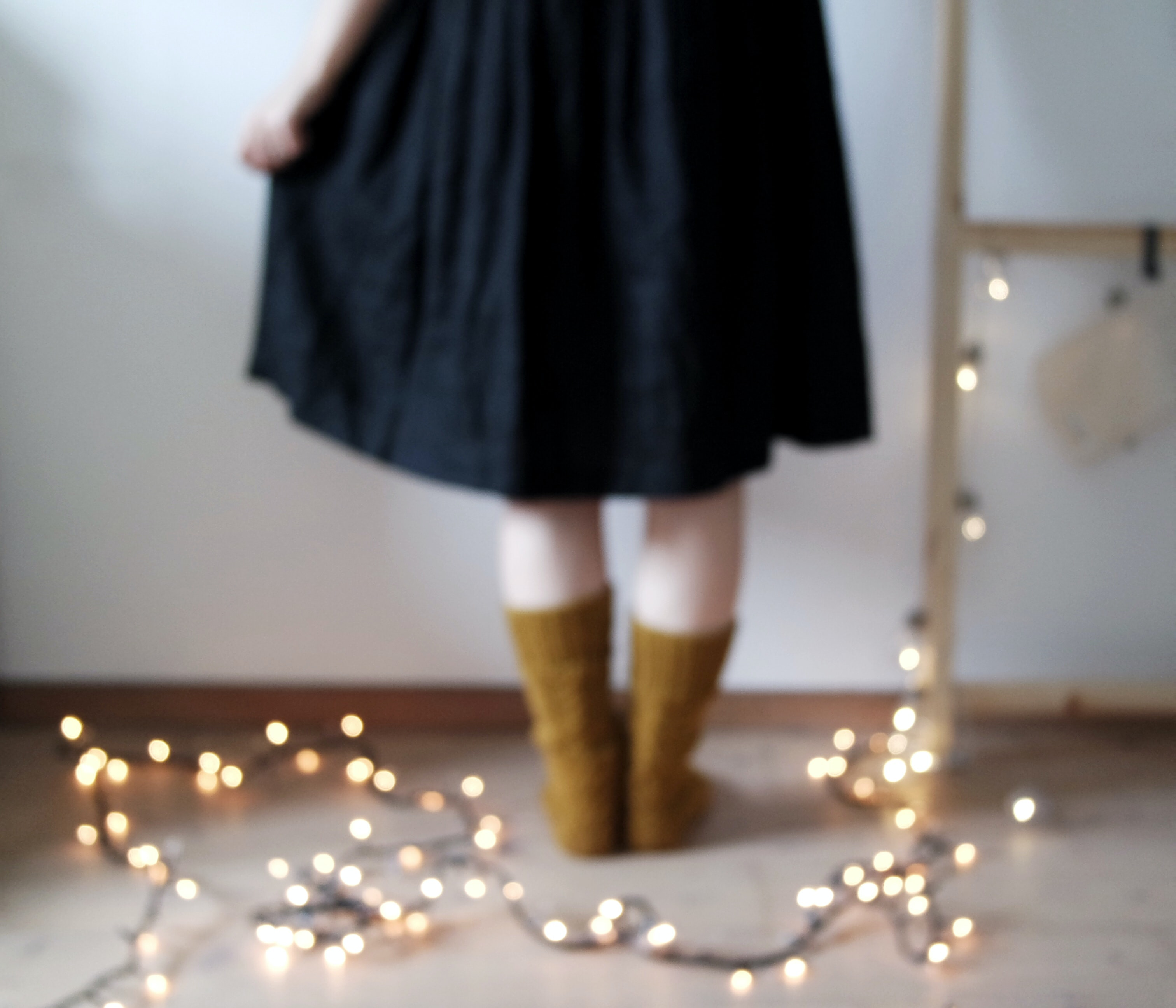 person standing beside string lights