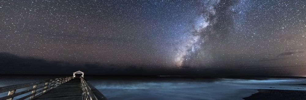 panoramic photography of footbridge leading to ocean under starry sky during nighttime