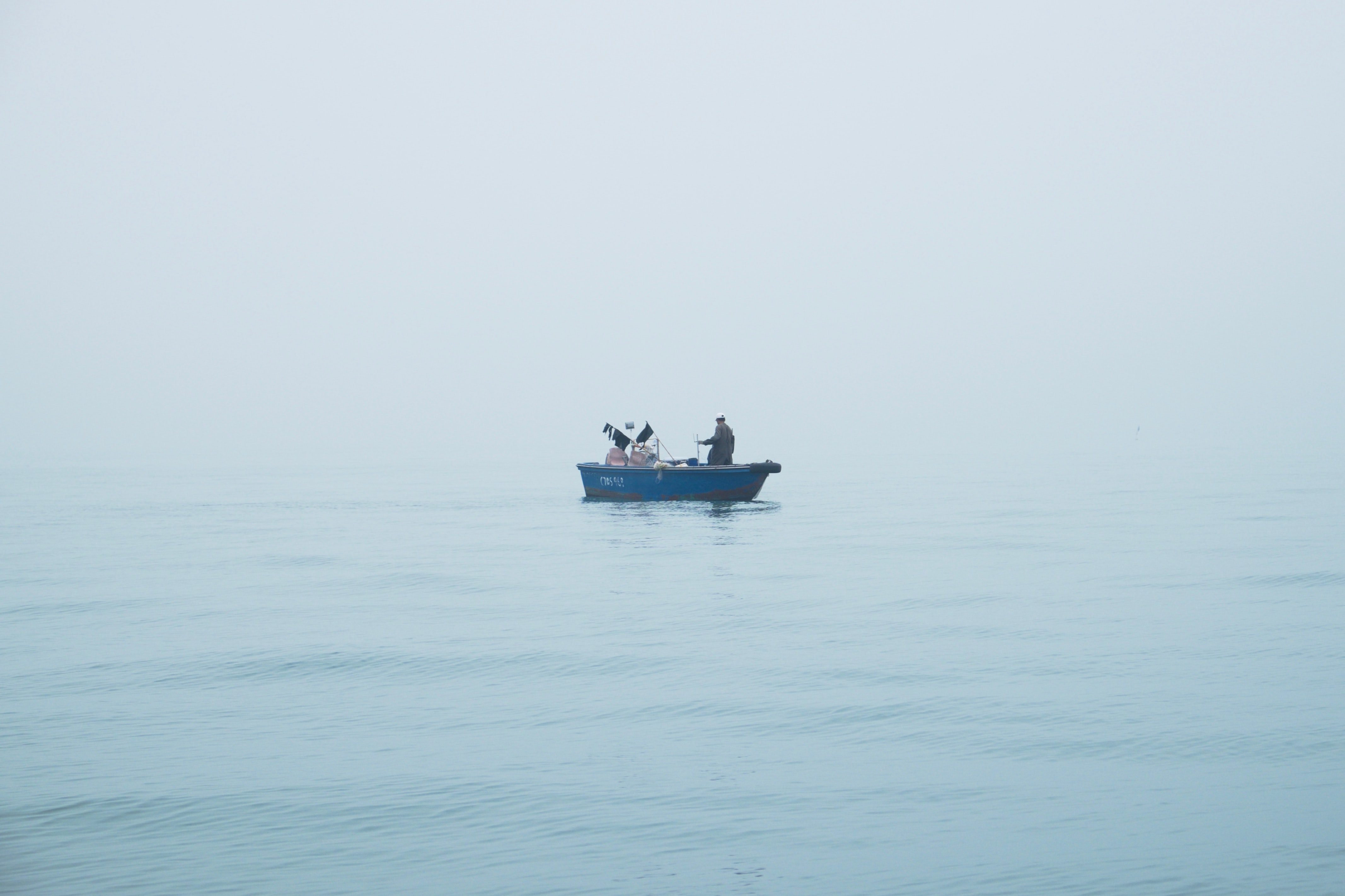 people riding blue boat on body of water
