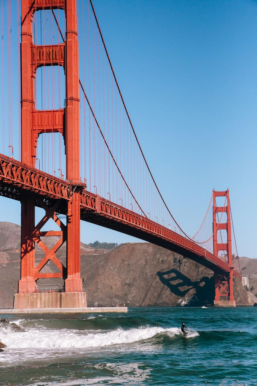 man surfing under Golden Bridge