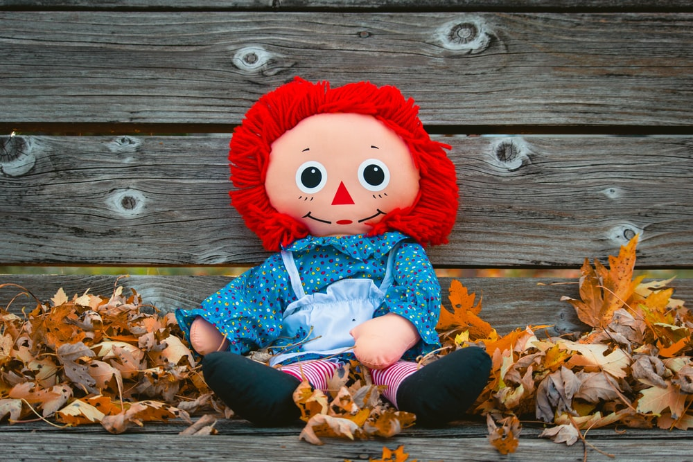 doll on gray wooden bench with maple leaves