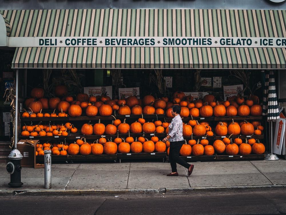 woman walking along pumpkin store