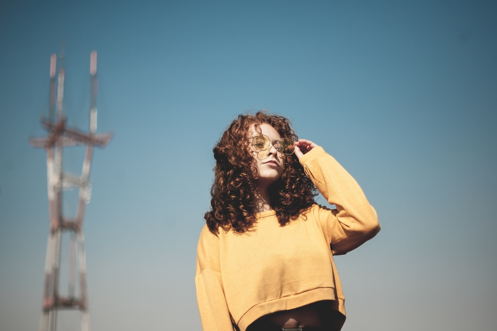 woman wearing sweater standing near tower