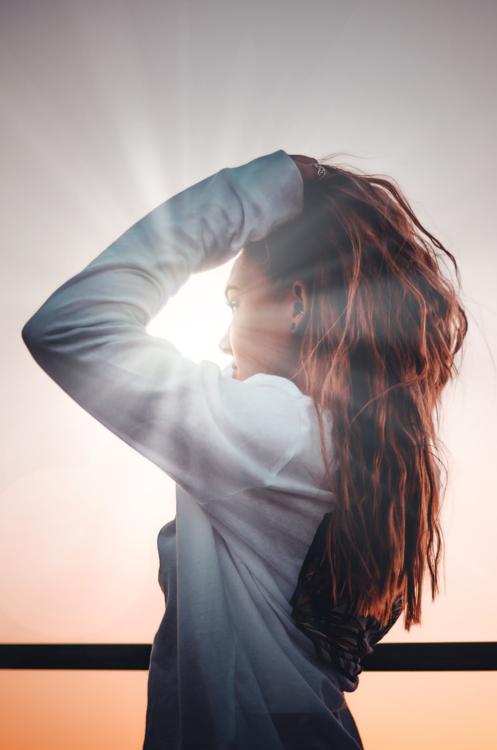 woman holding her hair during sunset