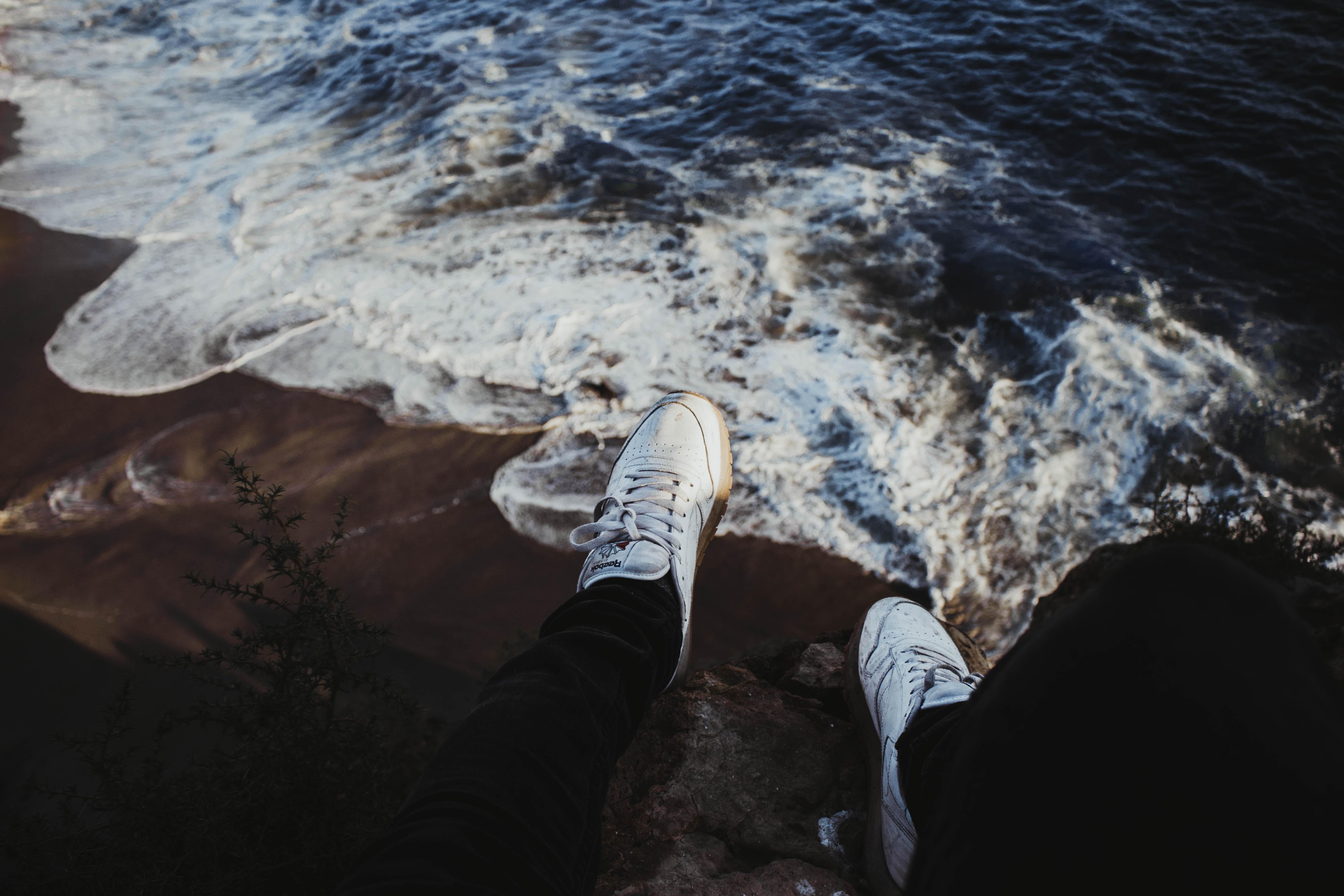 person sitting on rock near seashore