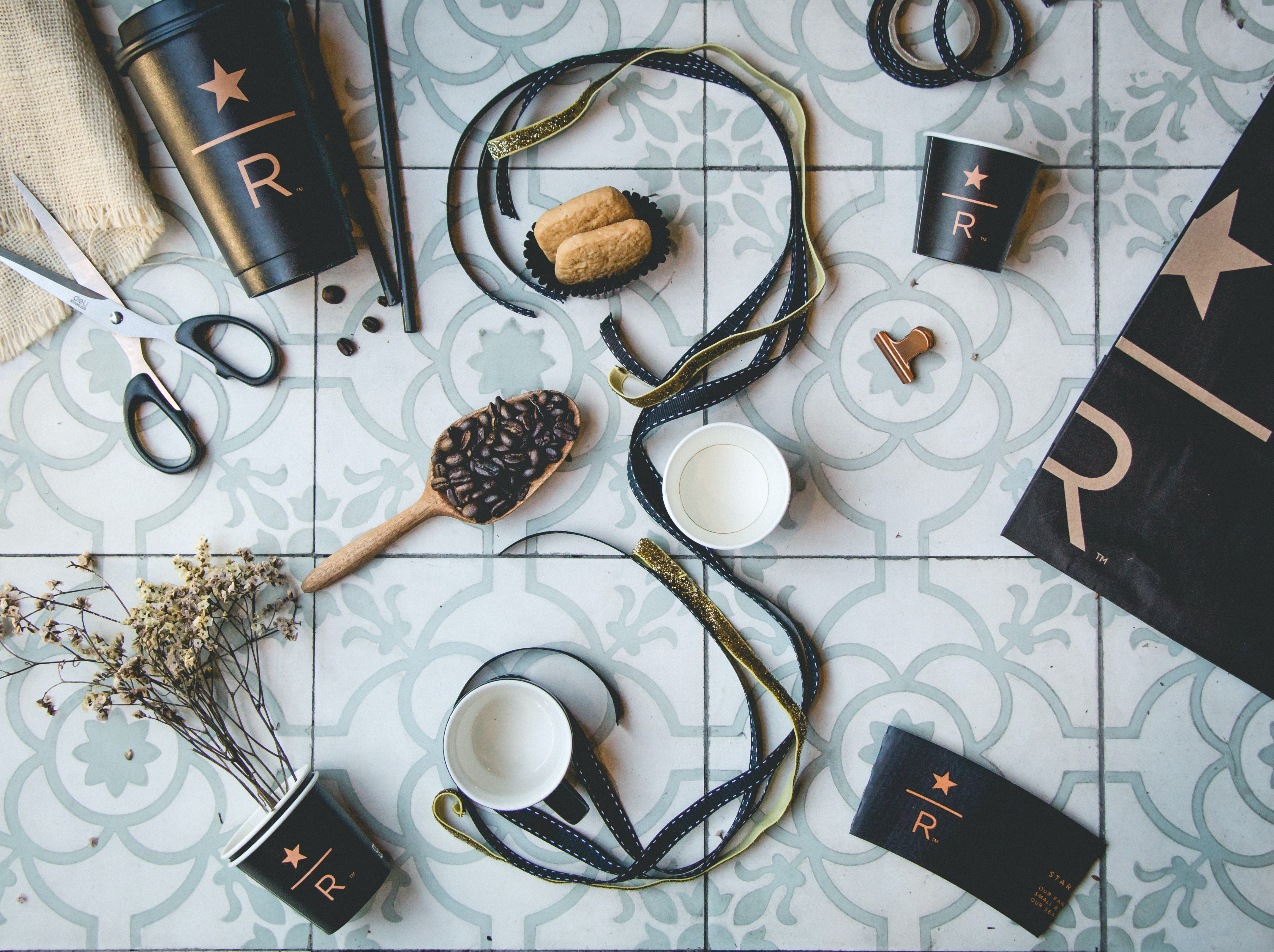 brown and black straps near coffee beans and cups on gray tiles