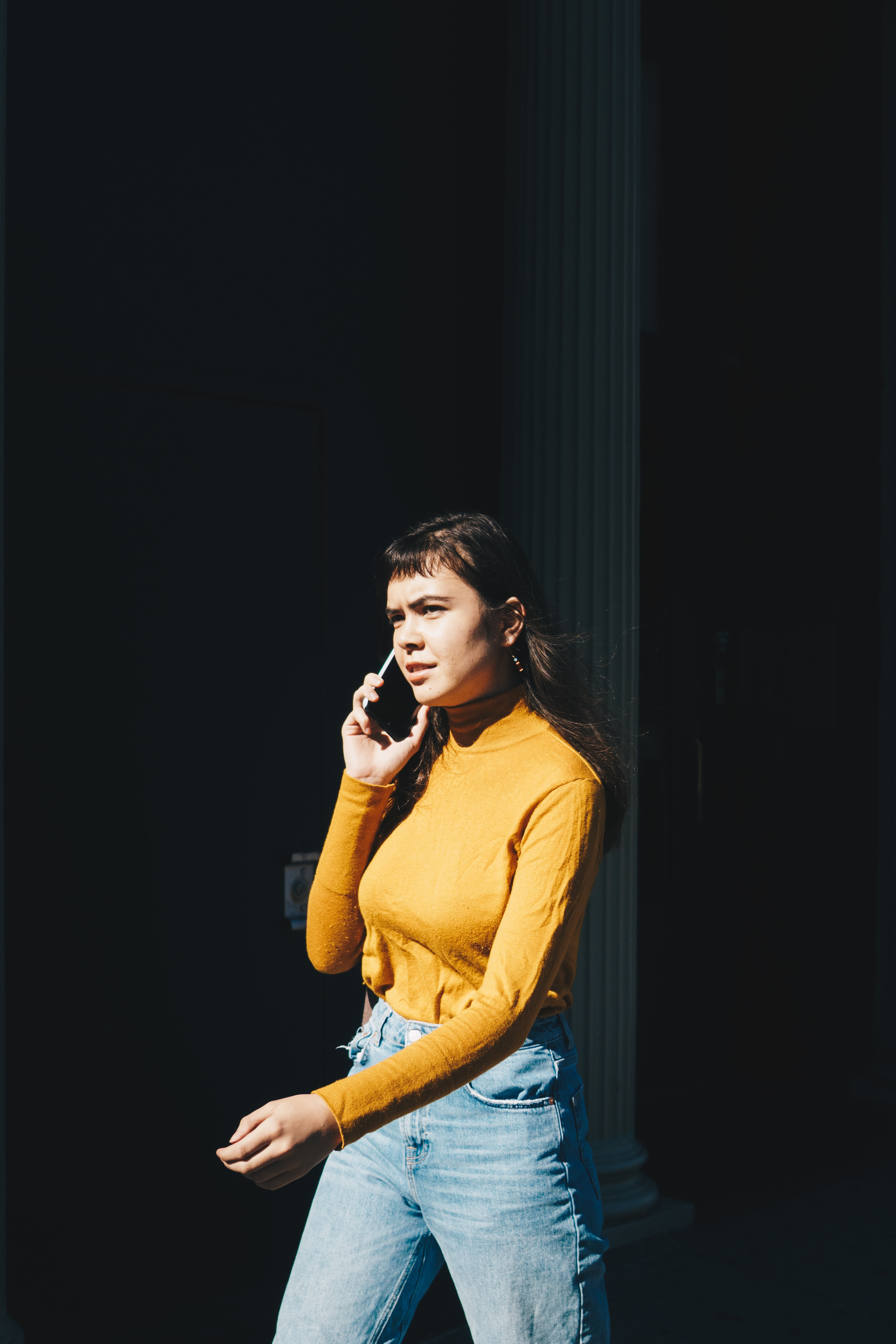 woman walking with phone on her right ear during daytime
