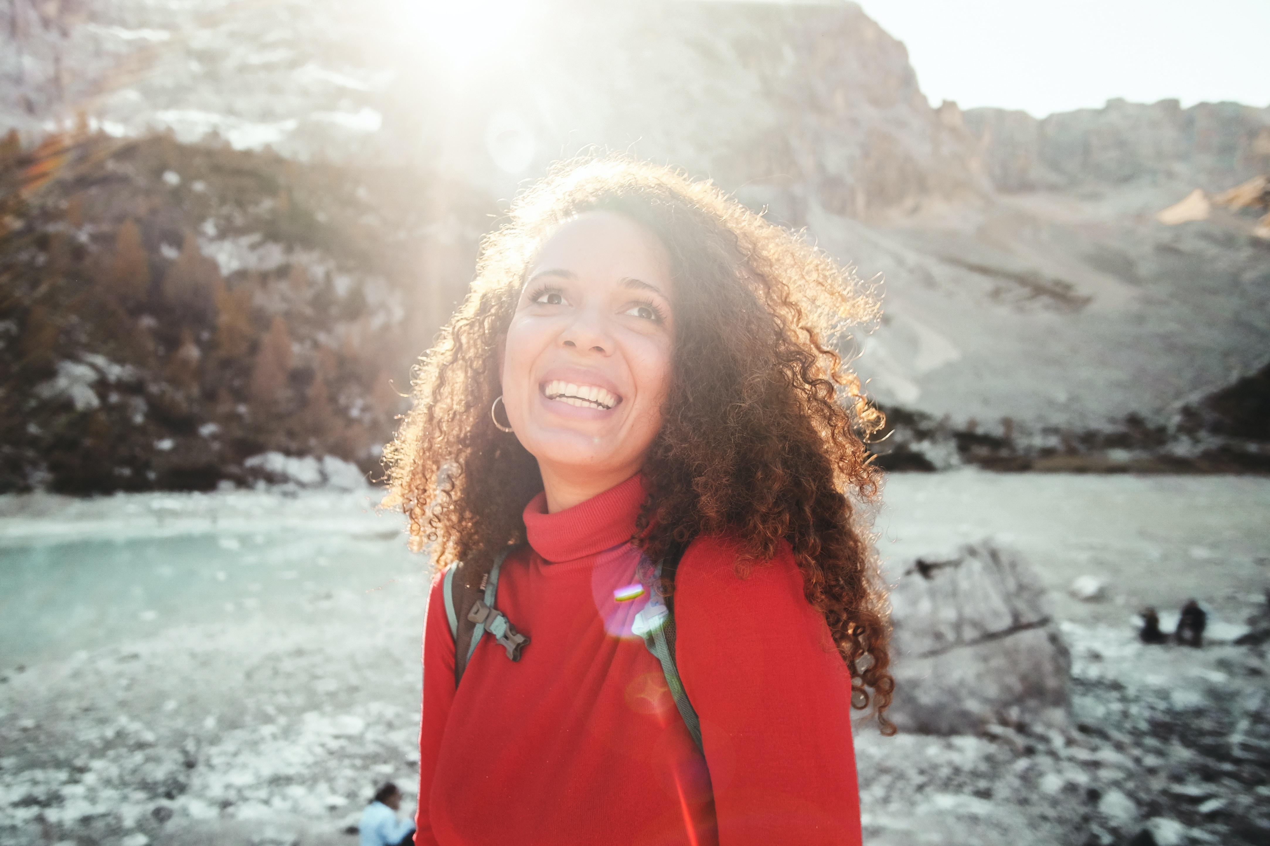 woman wearing red turtle neck shirt near mountain
