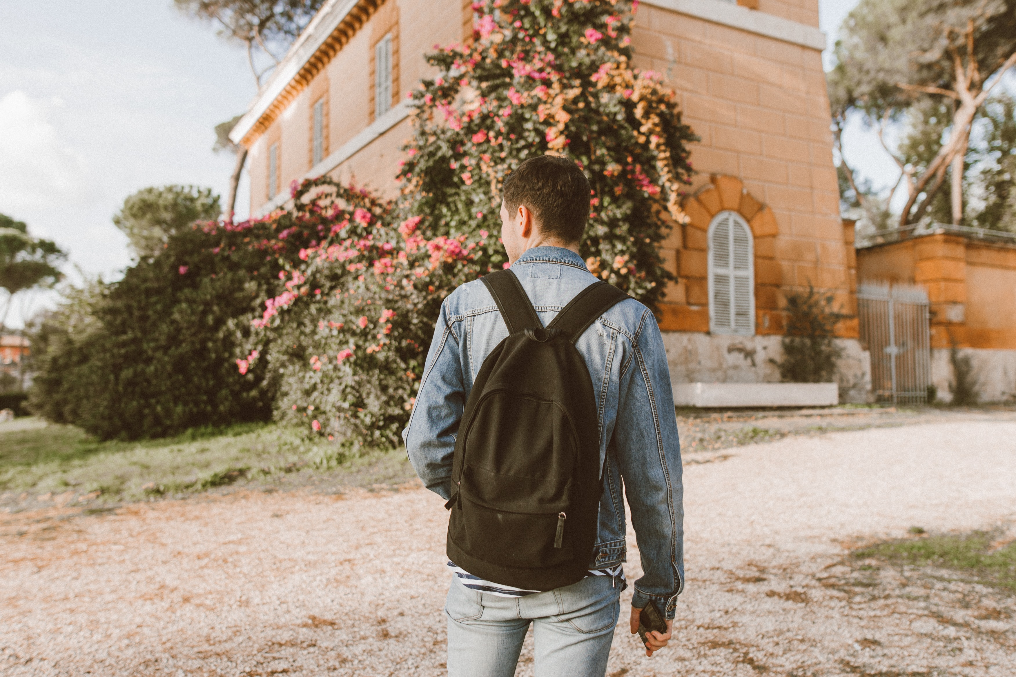 man with backpack standing in front of a house