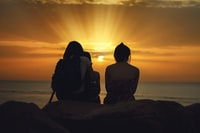 three person sitting on brown stone while watching the sunset