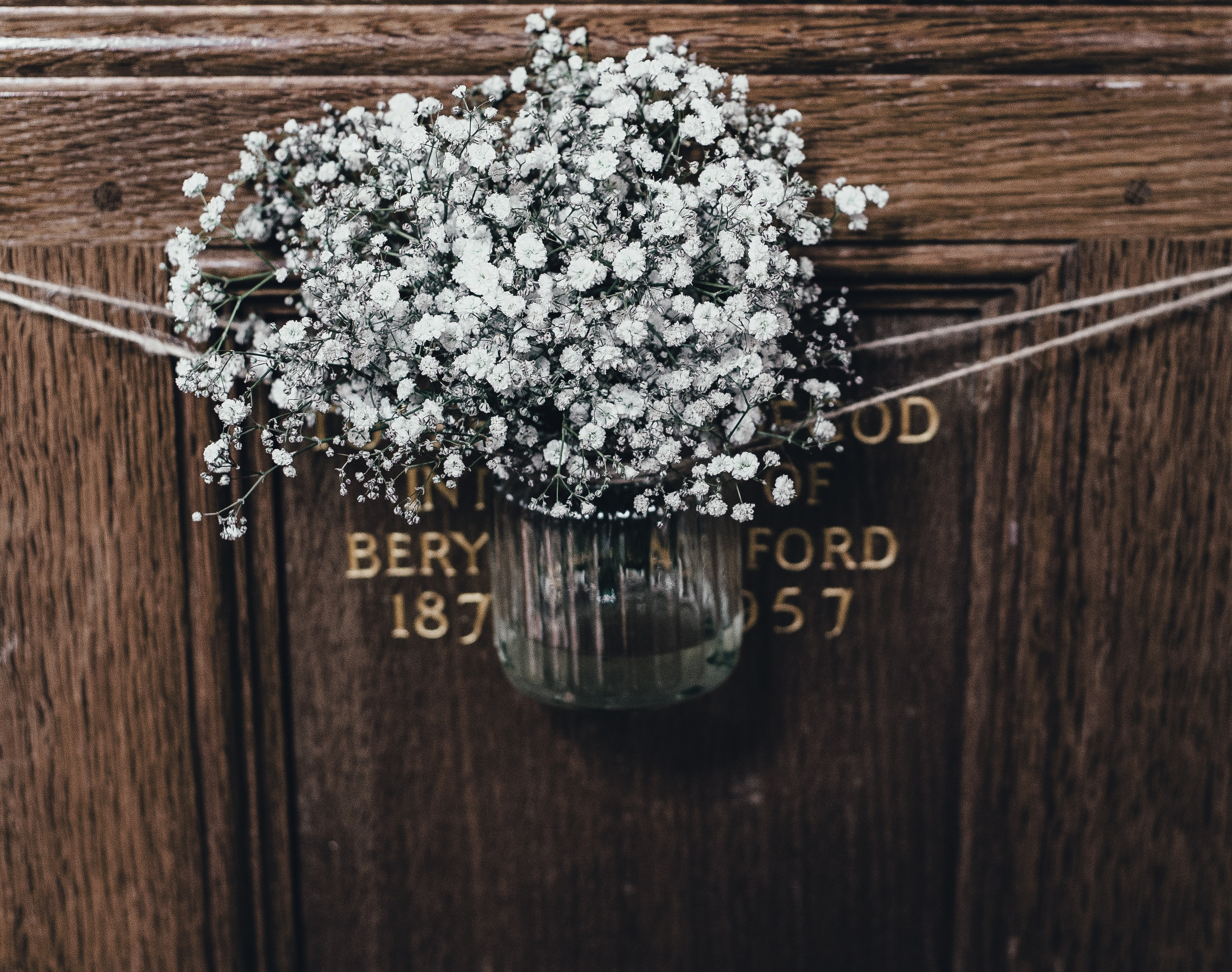 white flowers on clear glass vase hanging on door