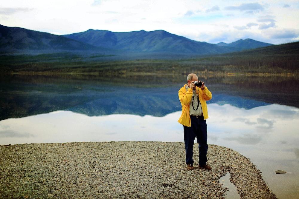 man in yellow jacket taking pictures during daytime