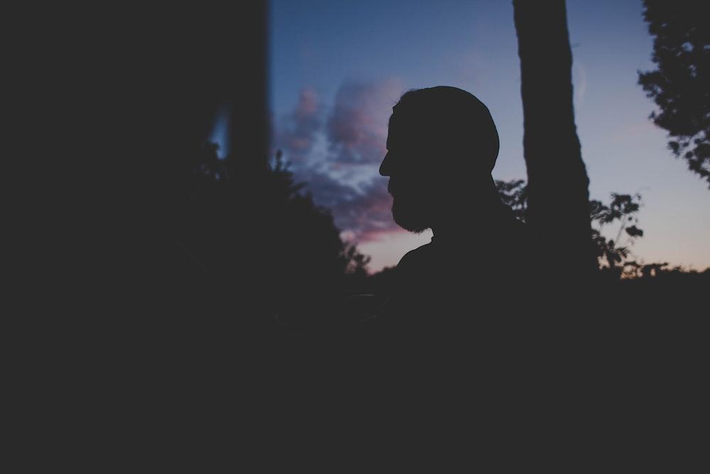 man standing near tree during night time