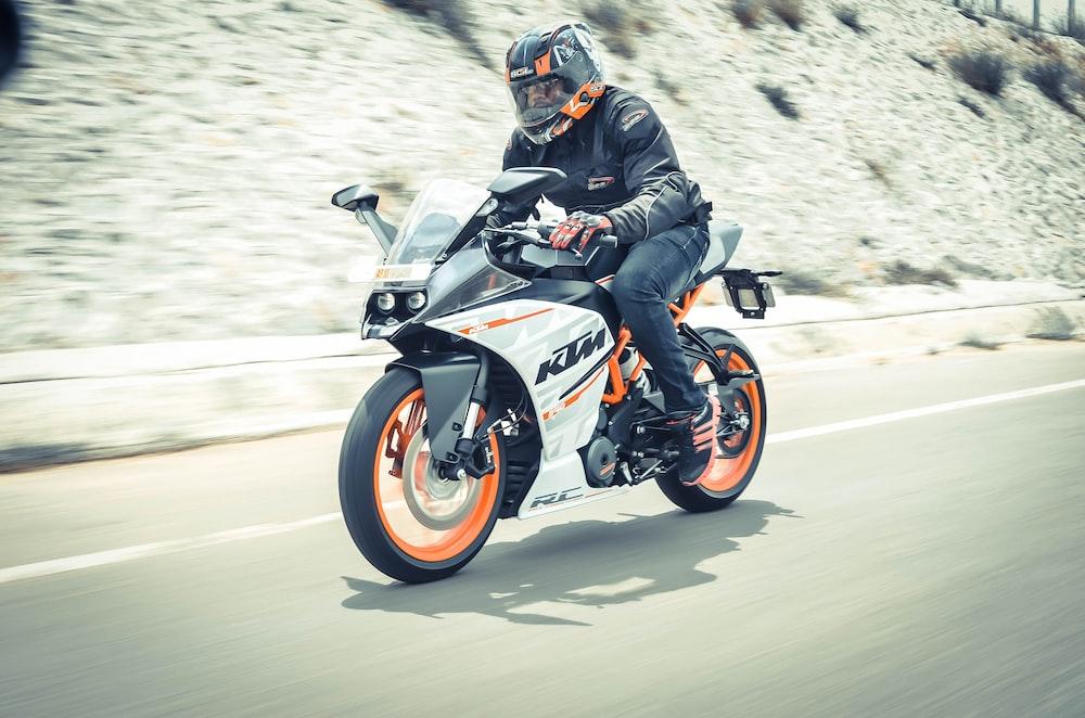 man riding white and orange KTM sports bike