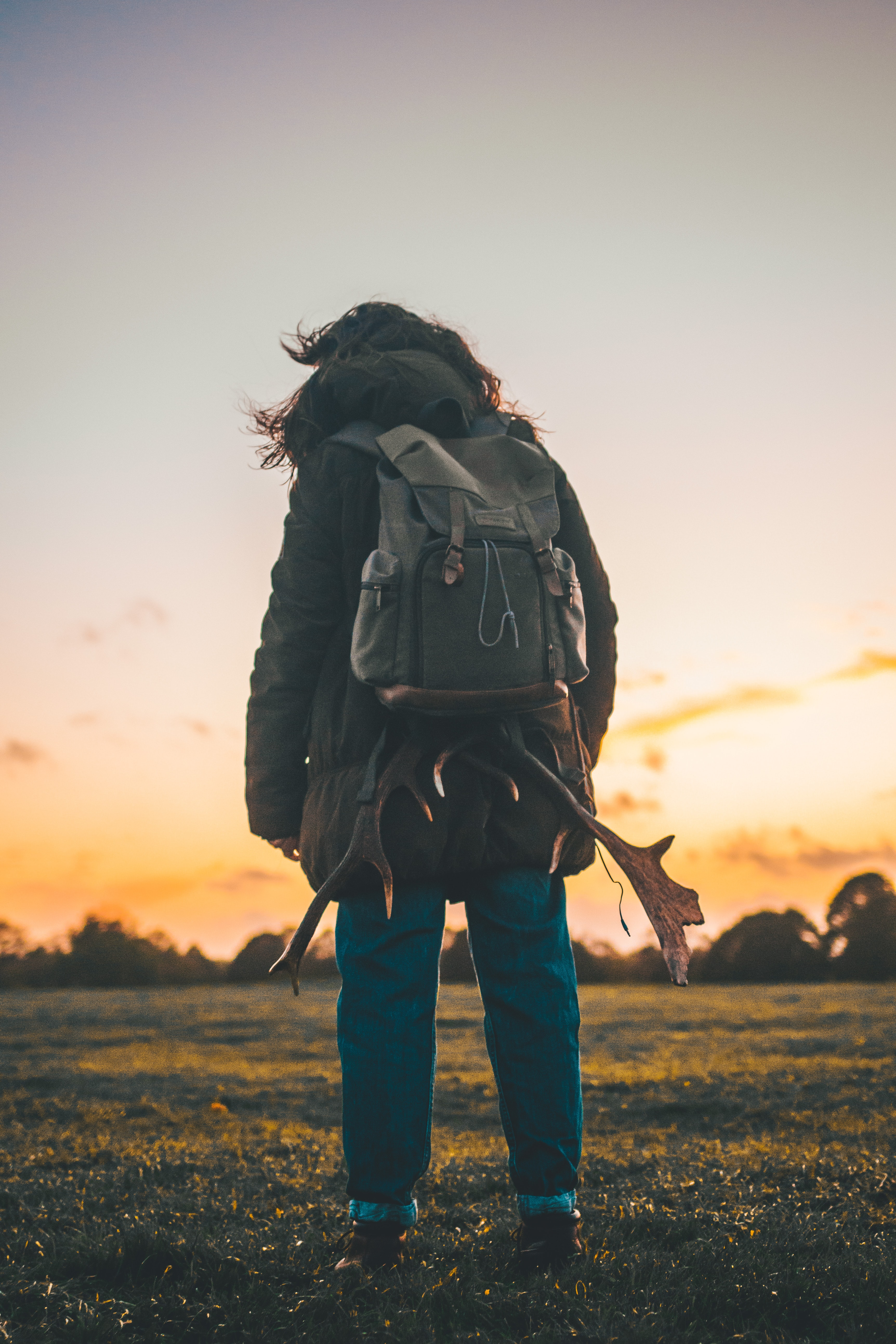 person wearing backpack standing on grass field