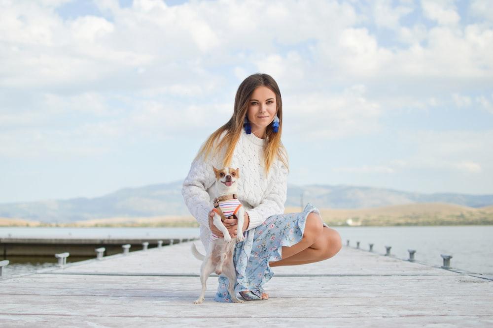 woman sitting beside dog on dock at daytime