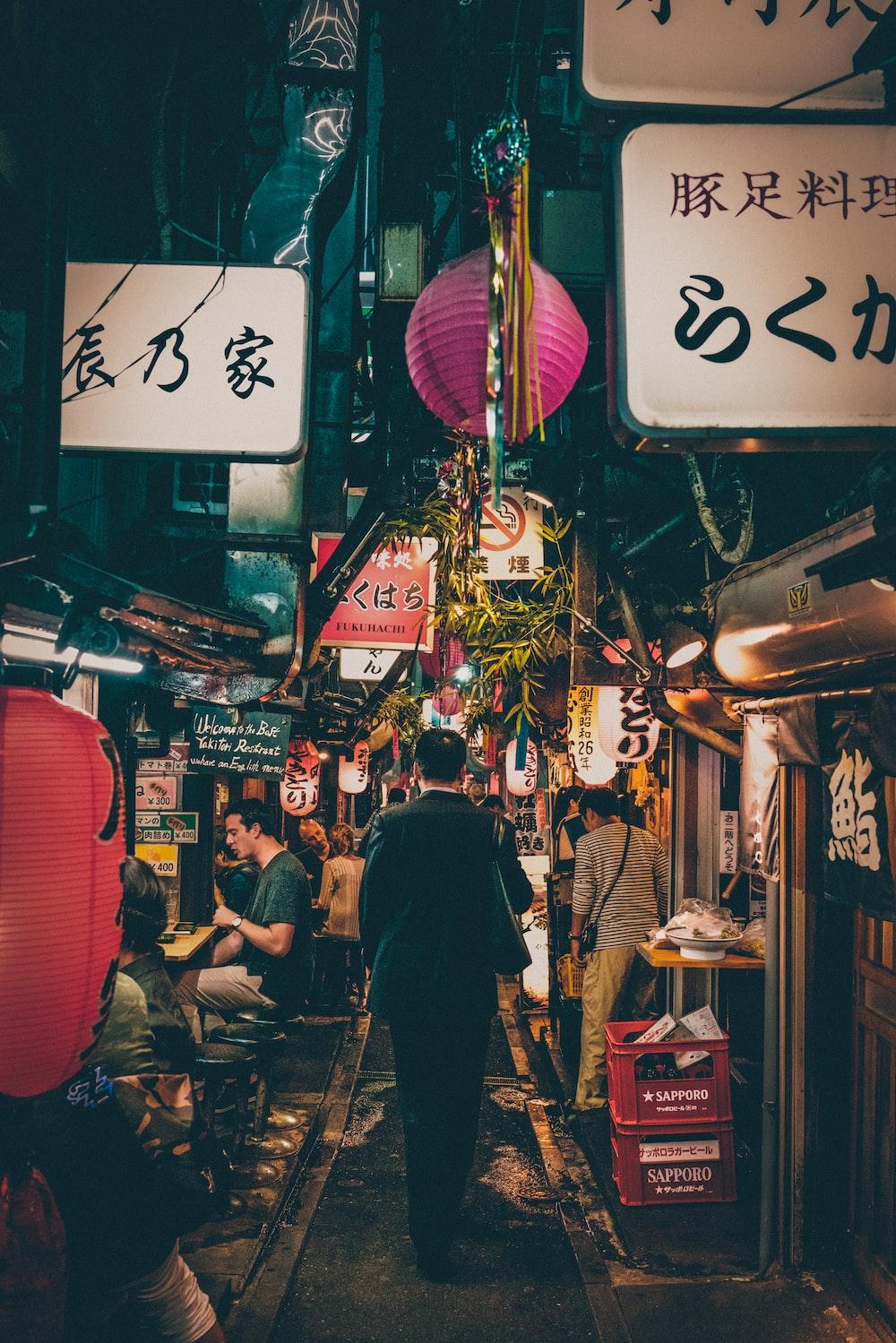 man walking between stores during night time