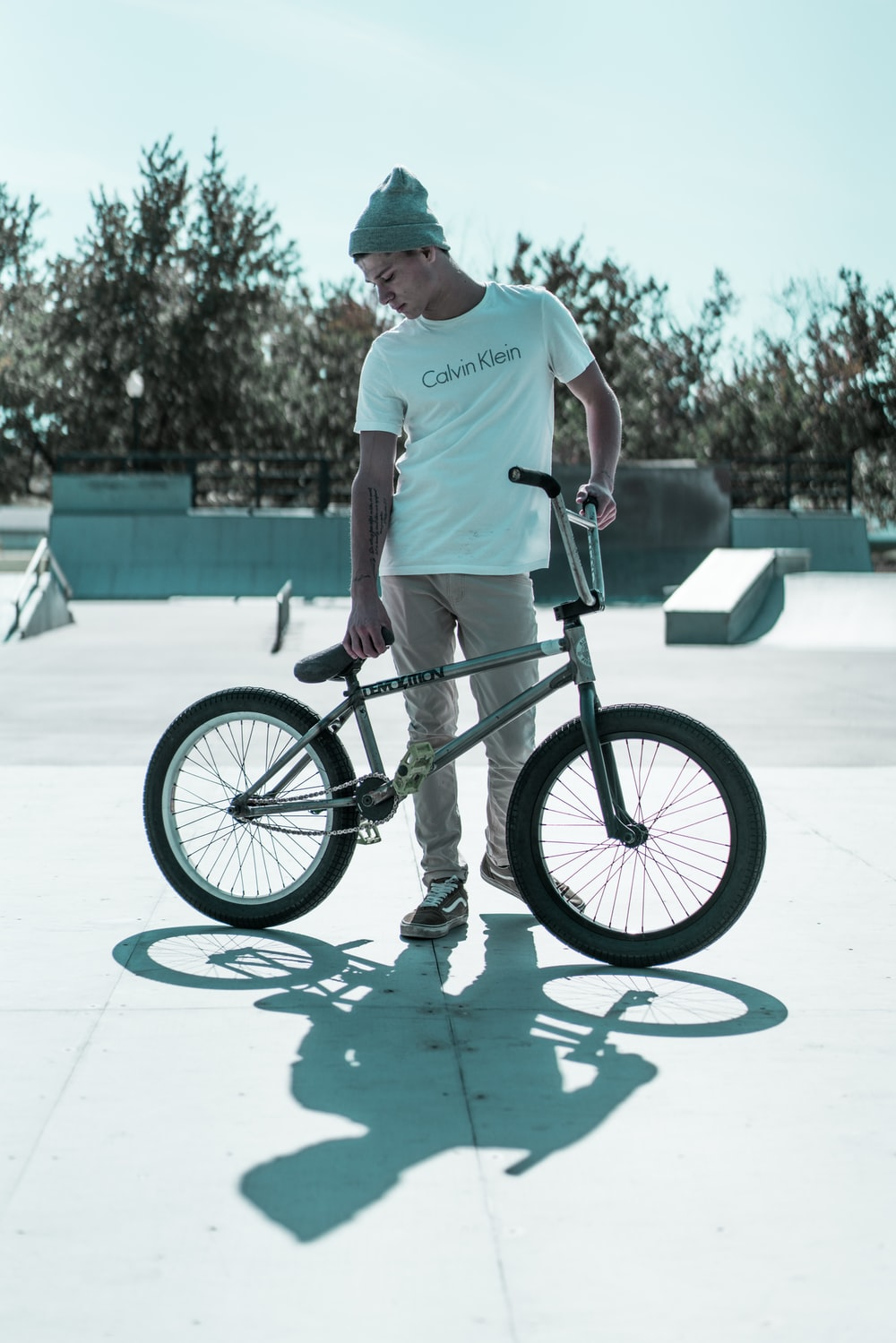 man standing and holding BMX bike