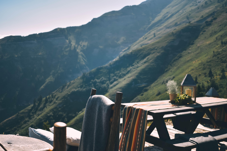 brown picnic table near mountain