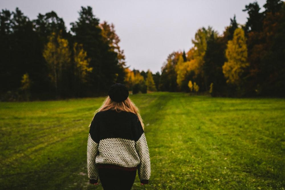 woman wearing sweater standing on green grass