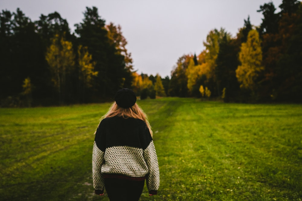 woman wearing sweater standing on green grass