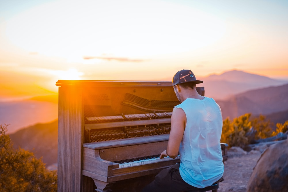 man playing piano outdoor during sunset