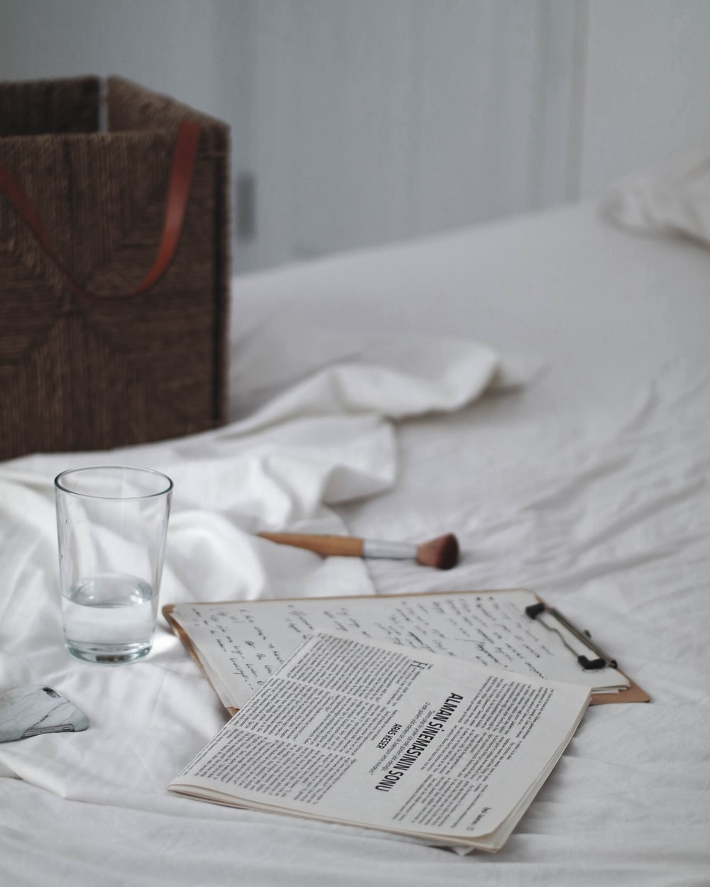 drinking glass beside clipboard on bed