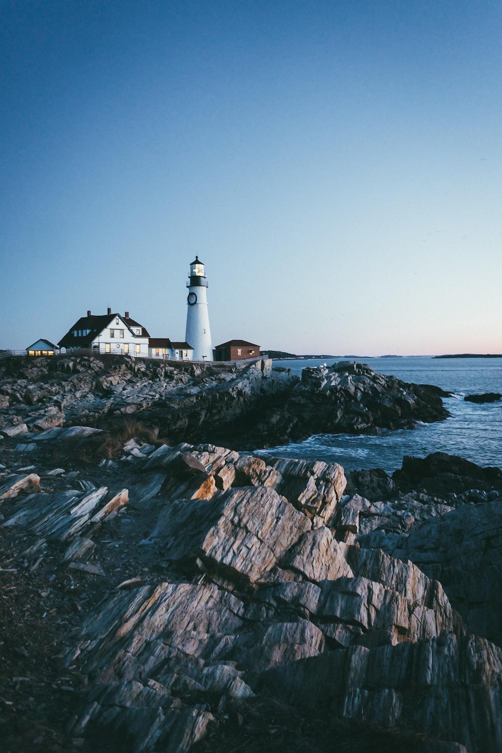 lighthouse beside body of water under blue sky