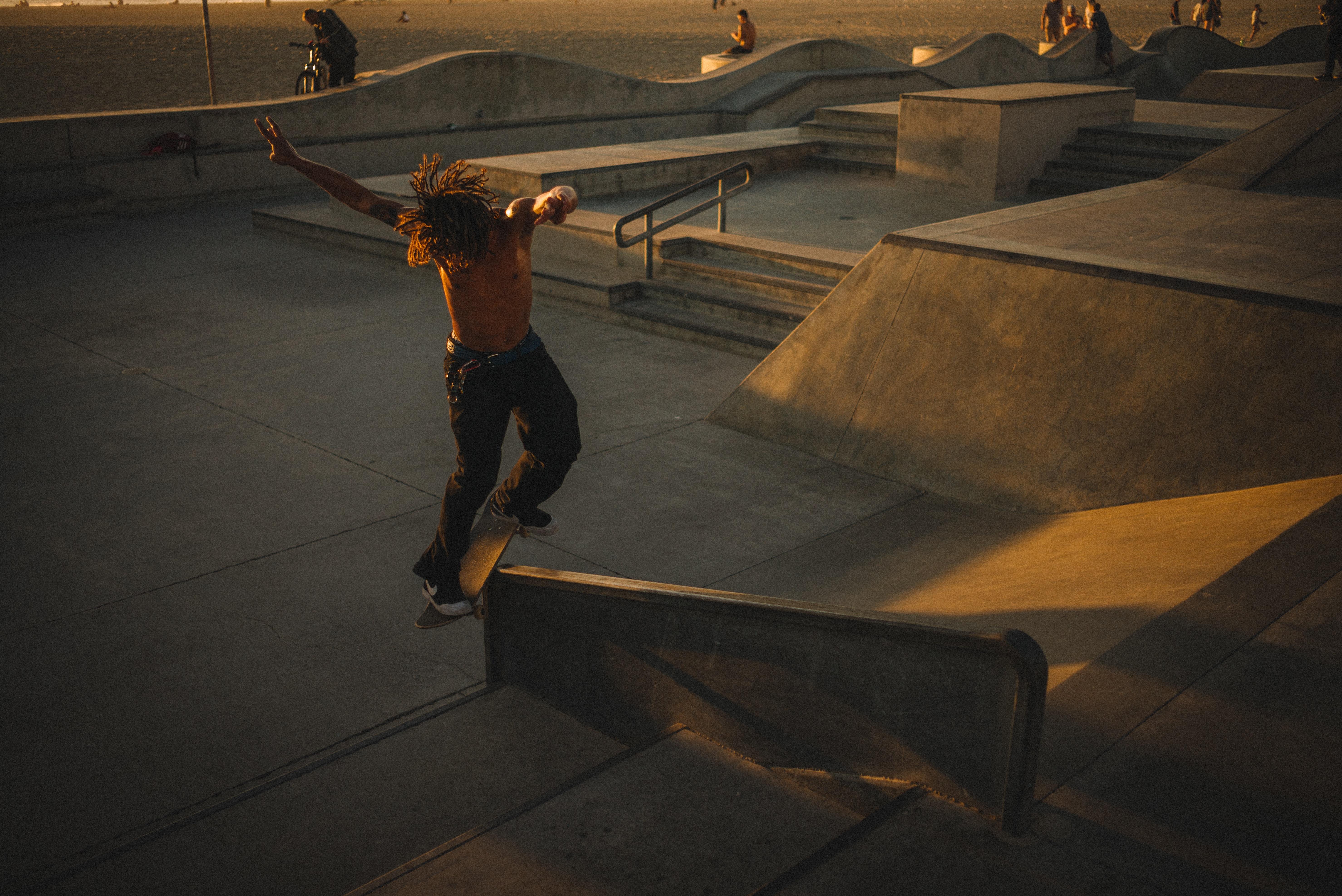 topless man doing skateboard tricks