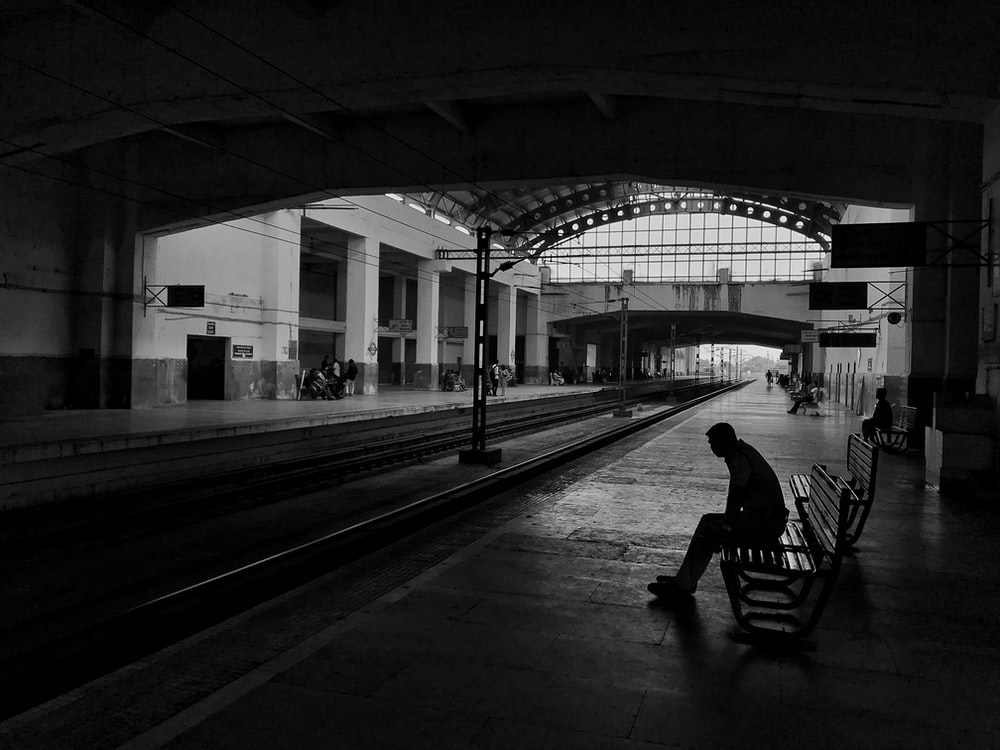 silhouette of man sitting on bench beside train rail
