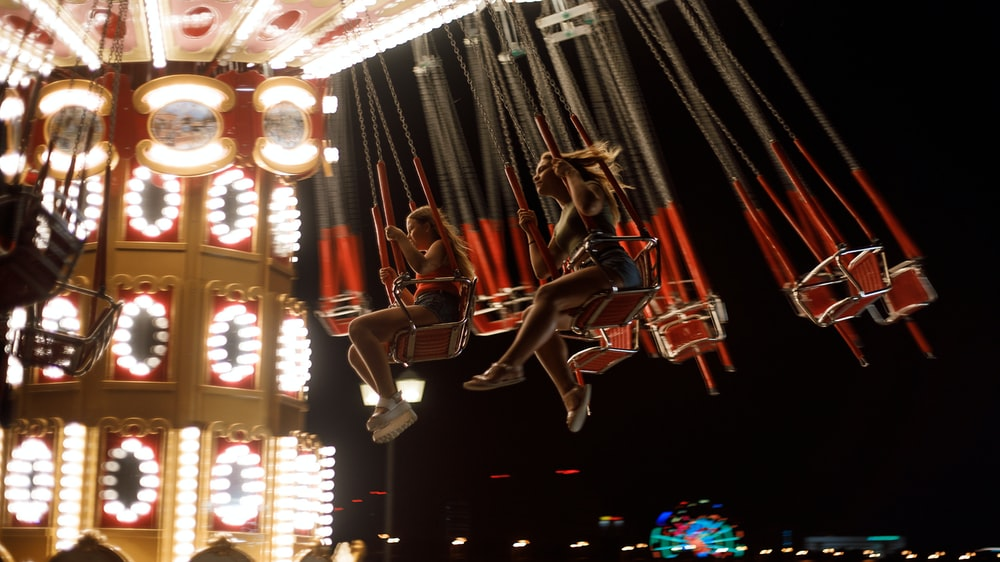 photo of woman riding on carousel