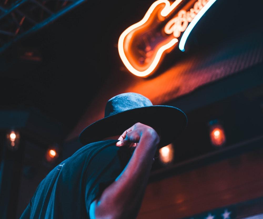 man standing under Budweiser signage at nighttime
