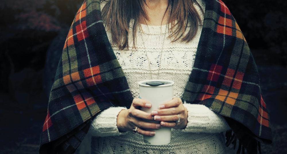femme tenant une tasse blanche chaude