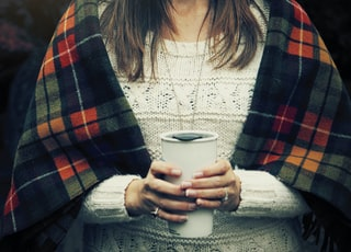 woman holding white cup